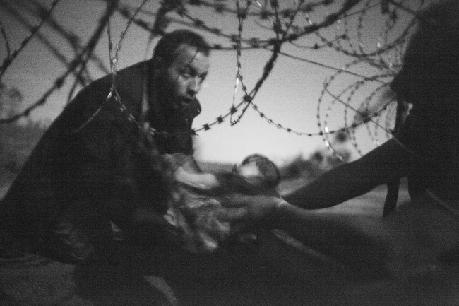 Migrants crossing the border from Serbia into Hungary. World Press Photo fo the Year