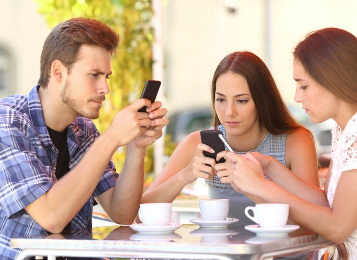 Online dating: group of young people sitting at table, using phones