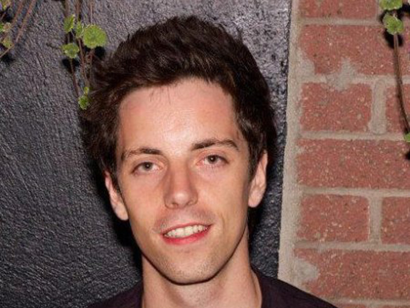 Headshot of a young man outside against a brick wall with strands of ivy.