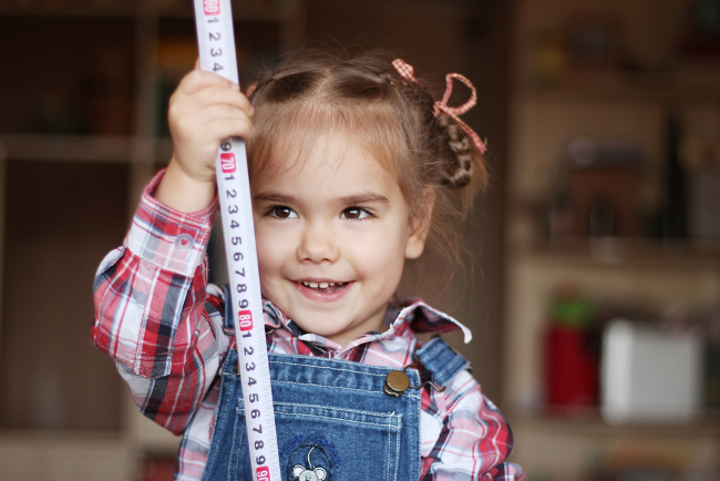 Maths: child measures herself with tape