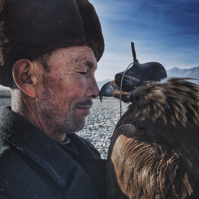 "'Man and the Eagle', by IPP's Grand Prize Photographer of the Year Siyuan Niu, based in China. ""The brave and wise Khalkhas live along the mountains in the south of Xinjiang and are companions with the eagles. They regard eagles as their children and train them for many years to hunt."" IPPAWARDS IPHONE"