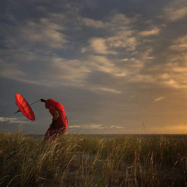 "'She Bends with the Wind' by Robin Robertis – ""I tend to bring a few things when I travel, one being this wonderful red umbrella. When others shoot the sunsets and beautiful scenery, I like to photograph some human aspects in these scenes."" IPPAWARDS iPhone"