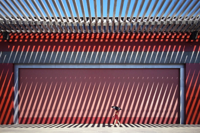 "'China' by Jian Wang – ""The photo 'China Red' was taken in Beijing Olympic Park, in front of this traditional Chinese red wall. I was fascinated by the great visual effect which was created by the lights and shades."" IPPAWARDS iPhone"