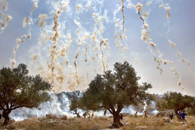 Israeli soldiers shoot tear gas during a demonstration against Israel's controversial separation barrier in the West Bank village of Nilin – image via Cris Toala Olivares, documentary single image winner at Magnum and LensCulture Photography Awards 2016