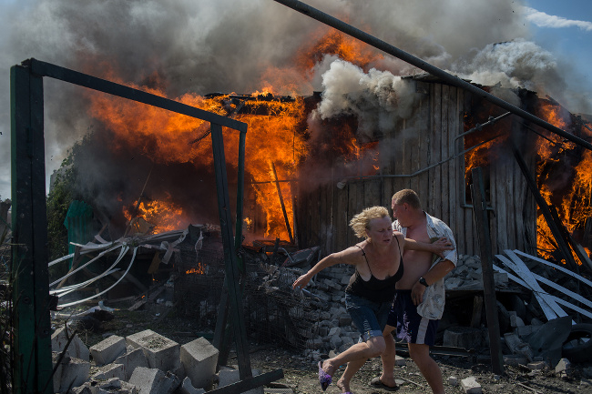 Civilians escape from a fire at a house destroyed by an air attack in Donbass, a village in Luhanskaya, eastern Ukraine – image via Valery Melnikov, photojournalism single image winner at Magnum and LensCulture Photography Awards 2016