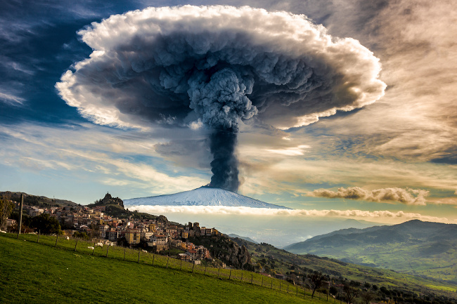An Etna eruption seen from San Teodoro. The quiet of the grazing flocks and the tranquility of the village are in contrast to the enormous explosive force of the volcano – image via Fernando Famiani, single image finalist at Magnum and LensCulture Photography Awards 2016