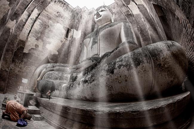 A monk paying homage to the Buddha statue of Wat Si Chum, Sukhothai Historical Park, Thailand. Image via Yakuzakorat/Wikimedia Commons