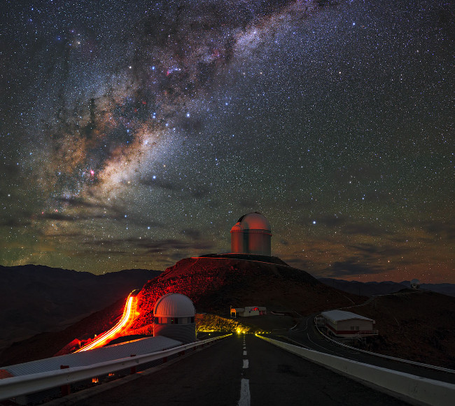 In this picture, our home galaxy the Milky Way stretches across the sky above the landscape of the Chilean Andes. In the foreground, the roads of ESO's La Silla Observatory are packed with state-of-the-art astronomical telescopes pointing towards, and far beyond, the Milky Way. Image via ESO/B. Tafreshi