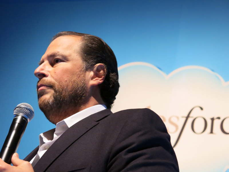 Marc Benioff stands in front of a Salesforce logo holding a microphone.