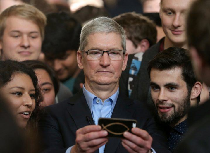 middle-aged man wearing glasses looking at iphone with crowd of young people behind him.