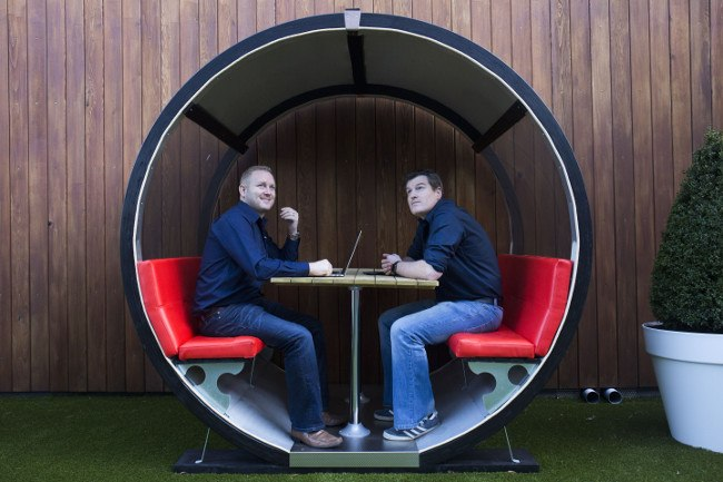 Two men in blue shirts and jeans sit inside a circular seating unit with red leather seats.