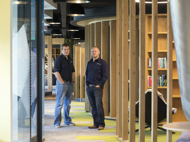 Two men in jeans and dark shirts stand in a corridor lined with wood and libraries in Cork.