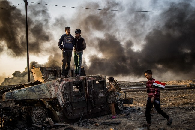 Taha Sirhan, 11, carrying the Iraqi flag through burned out oil fields in the city of Qayyarah south east of Mosul in Iraq. His dad was killed by ISIS during the occupation because he was working for the Iraqi police. Image: Asger Ladefoged, Denmark, Shortlist, Professional, Current Affairs & News, 2017 Sony World Photography Awards