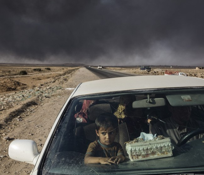 Iraqi civilians displaced by fighting in the village of Shora, 25km South of Mosul, reach an Iraqi army checkpoint on the Northern outskirts of Qayyarah. Image: Ivor Prickett, Ireland, Shortlist, Professional, Current Affairs & News, 2017 Sony World Photography Awards