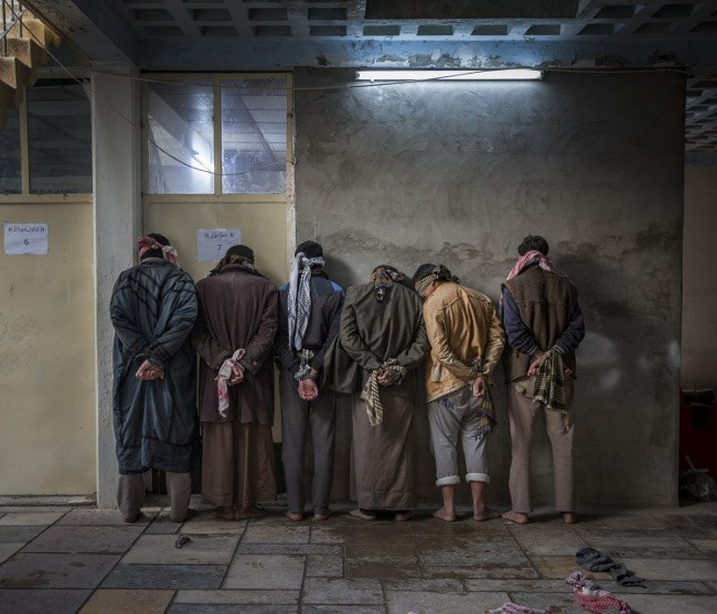 Iraqi men from the Hawija region of Iraq wait to be questioned by Kurdish security personnel at a base near Kirkuk. Having fled areas still under the control of ISIS militants, men and boys of fighting age are vetted for any links to the group before being allowed to join their families in camps for displaced people in the Kurdish-controlled region of the country. Image: Ivor Prickett, Ireland, Shortlist, Professional, Current Affairs & News, 2017 Sony World Photography Awards