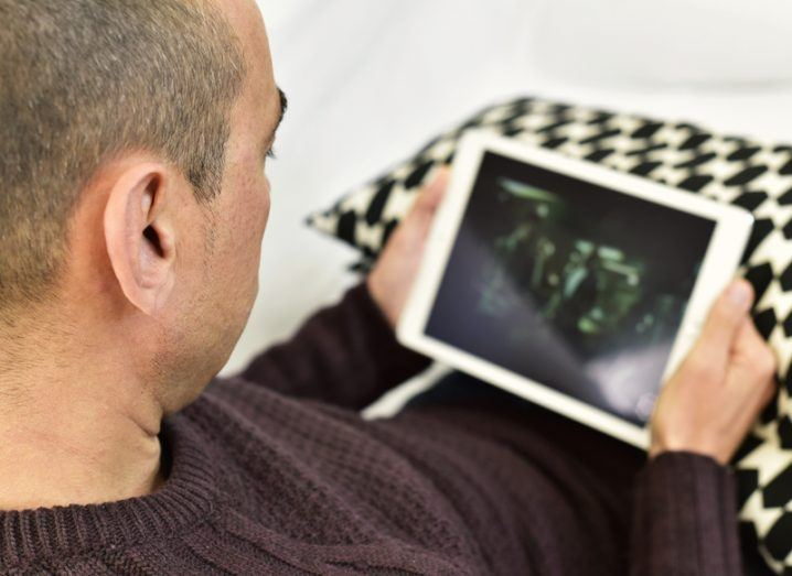 Man watching streamed content on tablet