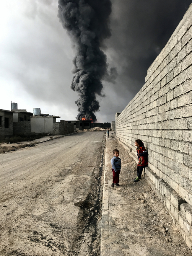 "Sebastiano Tomada, USA. Grand Prize winner – photographer of the year category, IPPA. Children of Qayyarah: ""Children roam the streets in Qayyarah, Iraq, near the fire and smoke billowing from oil wells set ablaze by Islamic State militants."""