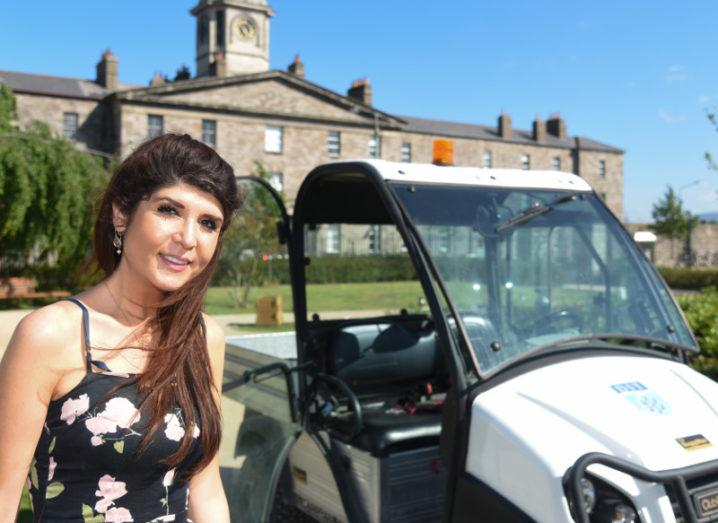 Ayda Esfandyari, PhD student in engineering at DIT beside one of the electric buggies on campus. Image: DIT