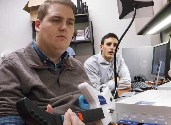 Battelle's Nick Annetta (right) watches as Ian Burkhart plays a guitar video game using his paralyzed hand. Image: The Ohio State University Wexner Medical Center
