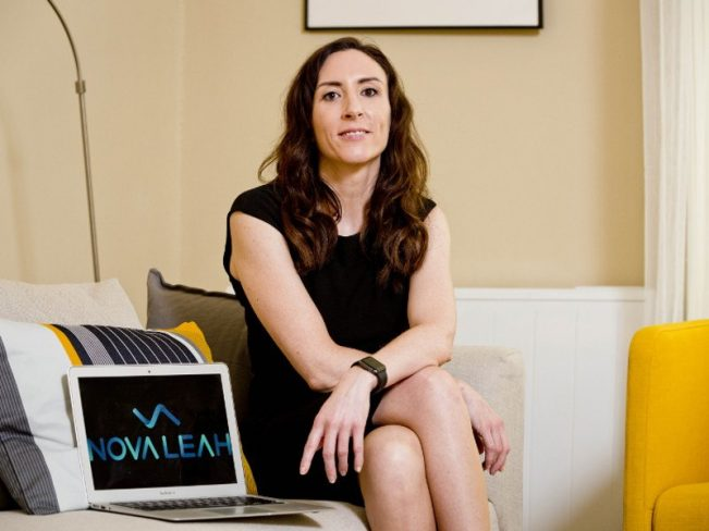 A woman in a black dress sits on a couch next to an open laptop displaying the Nova Leah logo onscreen.