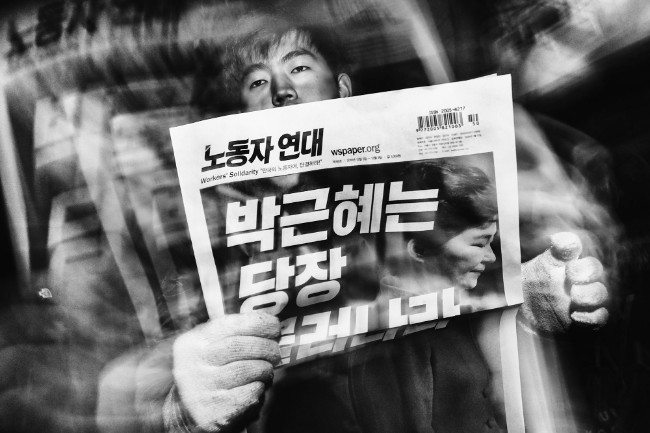"Read All About It. During a cold winter evening, a man sells Workers' Solidarity newspapers to protesters marching towards the presidential Blue House. The headline reads: ""Park Geun-hye Resign Now."" Image: Argus Paul Estabrook. Street Series Winner, Magnum and LensCulture Photography Awards 2017."
