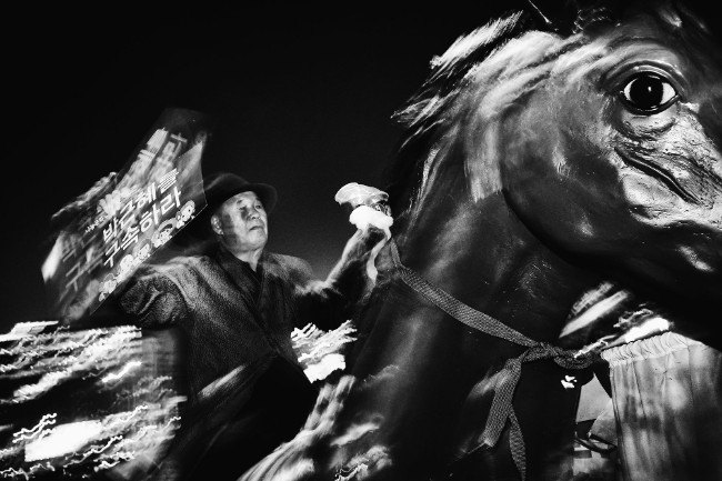 Dark Horse. A protester rides a fiberglass horse in Gwanghwamun Square to deliver his message to others. Throughout the many public demonstrations, the largest one had an estimated 1.7 million participants. Image: Argus Paul Estabrook. Street Series Winner, Magnum and LensCulture Photography Awards 2017.
