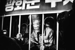 "Behind Bars. ""Imprisoned and surrounded by journalists, a protester plays President Park Geun-hye during the Christmas Eve demonstration in Seoul, South Korea."" Image: Argus Paul Estabrook. Street Series Winner, Magnum and LensCulture Photography Awards 2017."