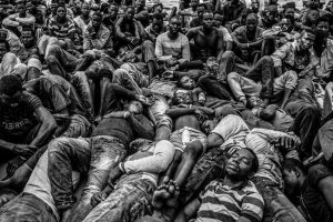 Gambian and other West African migrants lay exhausted on the deck of the Migrant Offshore Aid Station ship after being rescued from a packed rubber boat that was starting to sink off the coast of Libya. Image: Jason Florio. Photojournalism Series Winner, Magnum and LensCulture Photography Awards 2017.