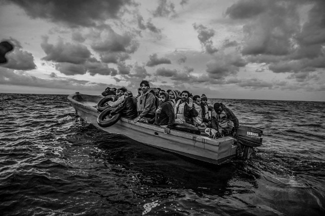 At dawn a small wooden boat carrying 21 Bangladeshis and one Congolese is spotted drifting in international waters by Migrant Offshore Aid Station. The engine had broken down, and the migrants, who had set out before midnight from Libya, had been floating without direction or means of communication throughout the night. Image: Jason Florio. Photojournalism Series Winner, Magnum and LensCulture Photography Awards 2017.