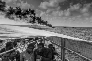 Gambian and other West African migrants just rescued from a packed rubber boat off the coast of Libya huddle on the deck of Migrant Offshore Aid Station's ship. In the background, their rubber boat is set ablaze to prevent smugglers, who were circling during the rescue, from taking the engine and boat back to Libya to use again. Image: Jason Florio. Photojournalism Series Winner, Magnum and LensCulture Photography Awards 2017.