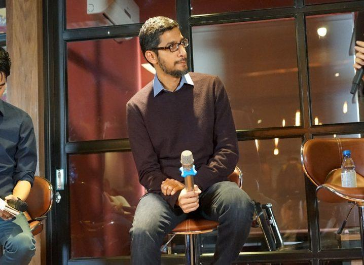 Indian man in brown jumper and blue shirt sitting and holding a microphone during a panel discussion.