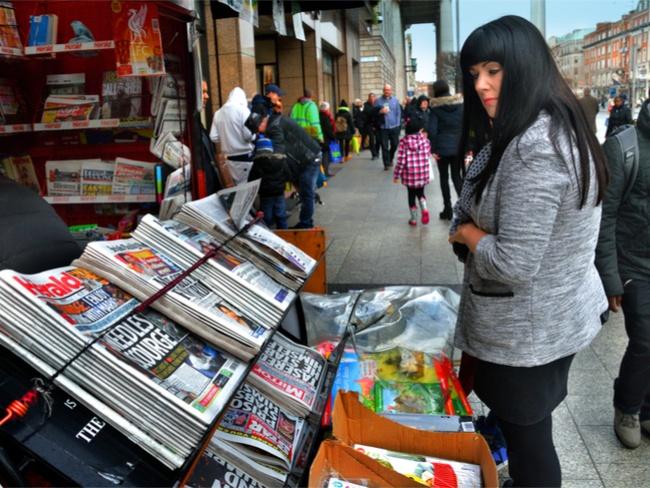 A woman reads newspaper headlines at a newsstand along O'Connell Street, Dublin. Image: Owen J Fitzpatrick/Shutterstock