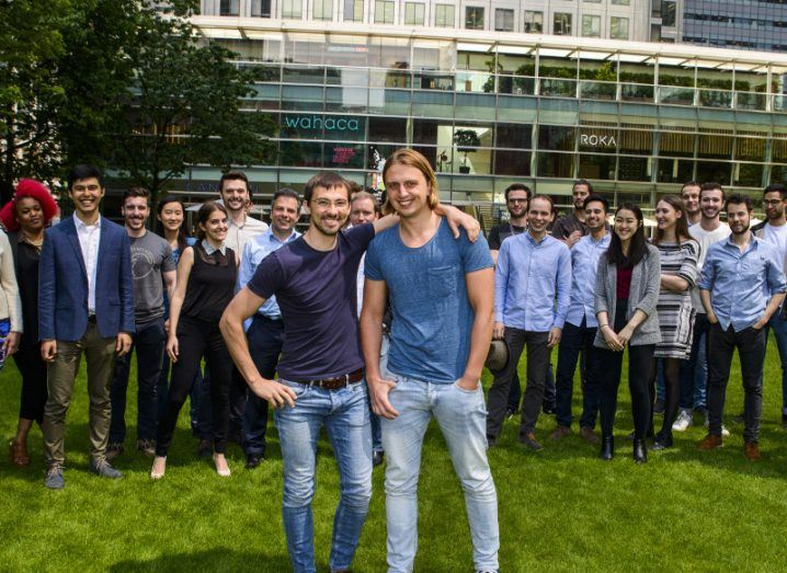Revolut co-founders stand in front of a large team of people in a park.