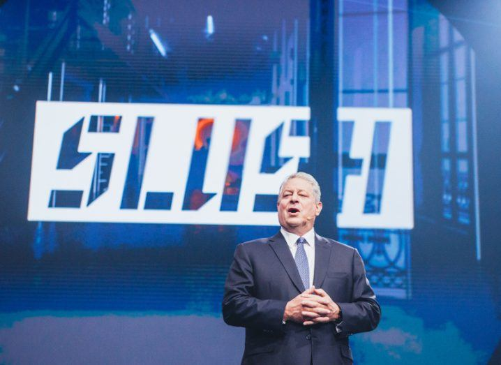Al Gore speaking on stage in front of blue background with sign that says Slush.