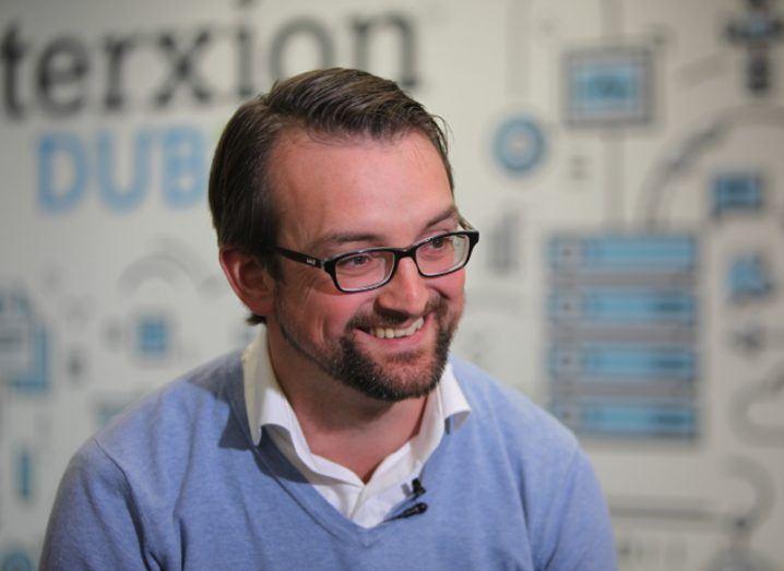 Man in blue jumper wearing glasses smiling.