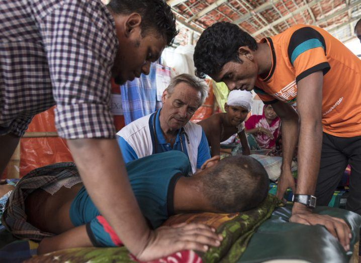 Rohingya crisis: Dr Ian Cross speaks with a patient with a gunshot wound in his lower back at MSF's medical facility in Kutupalong, Bangladesh. Image: Paula Bronstein/MSF