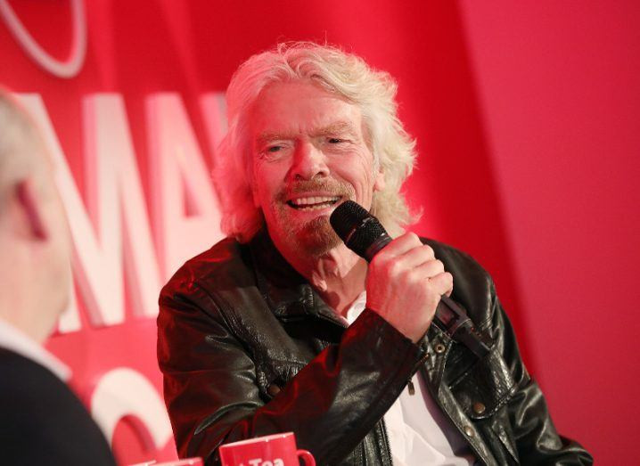 Richard Branson sits on a stage talking into a microphone.