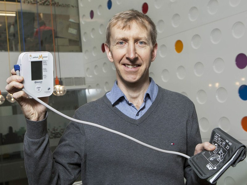 In one hand, a man holds aloft a device connected to a blood pressure monitoring armband in his other hand.