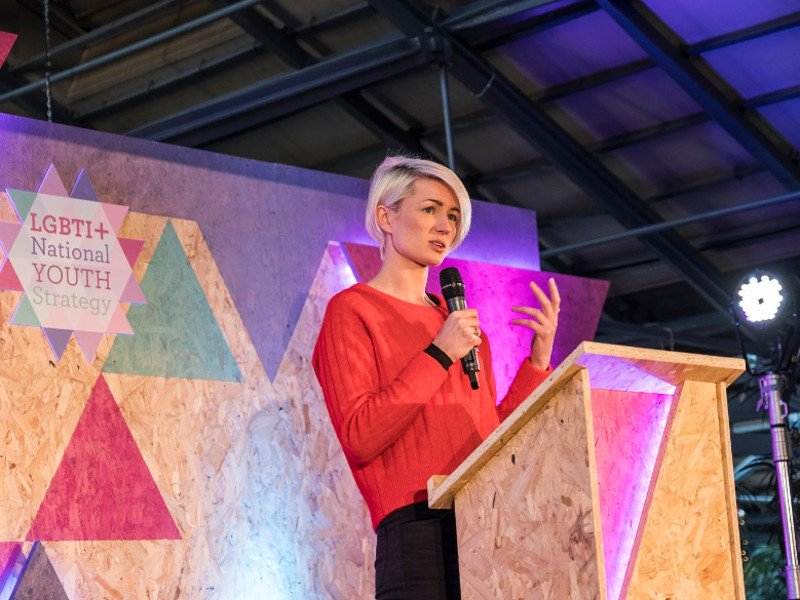 A woman with short blonde hair holds a mic at a woodchip podium on a stage decorated with colourful triangles.
