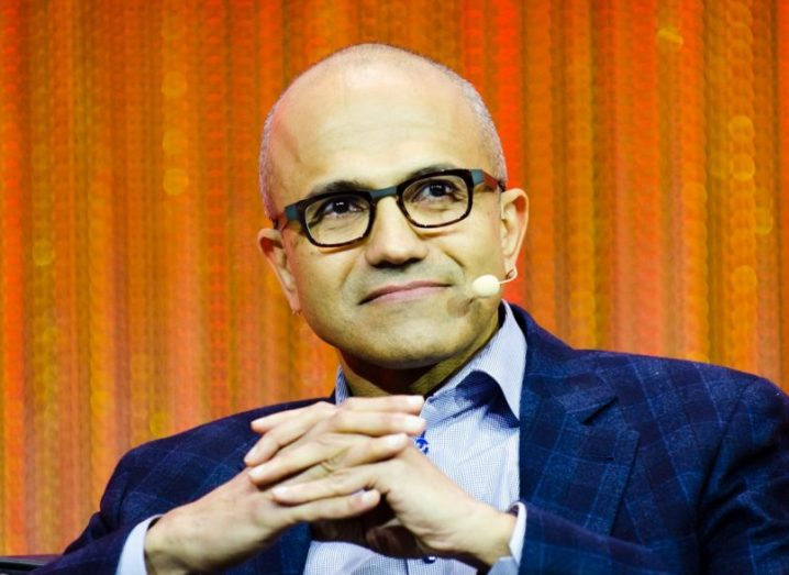 Satya Nadella sits on a stage wearing a microphone up to his face.