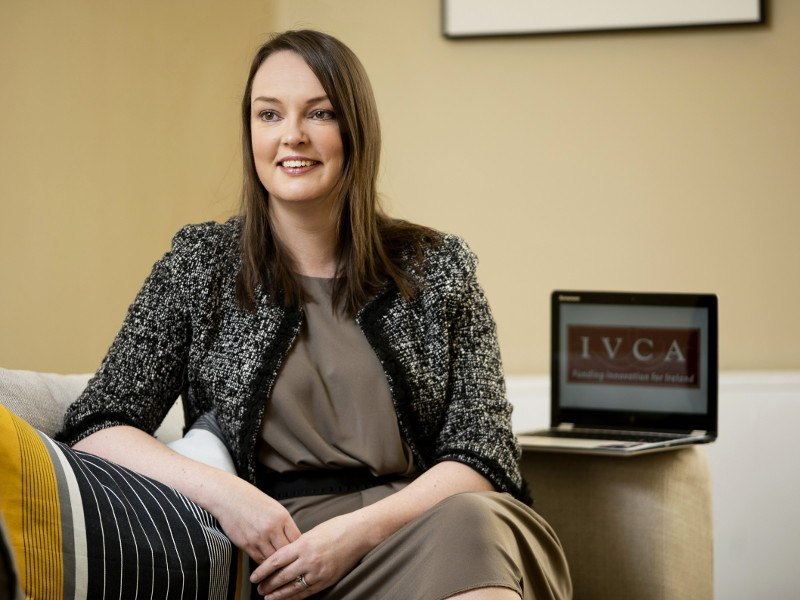 A woman in a brown dress sits on a couch with a laptop open next her displaying the IVCA logo.