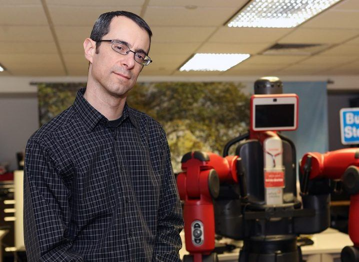 Aaron Steinfeld in a black shirt standing in front of robotic equipment.