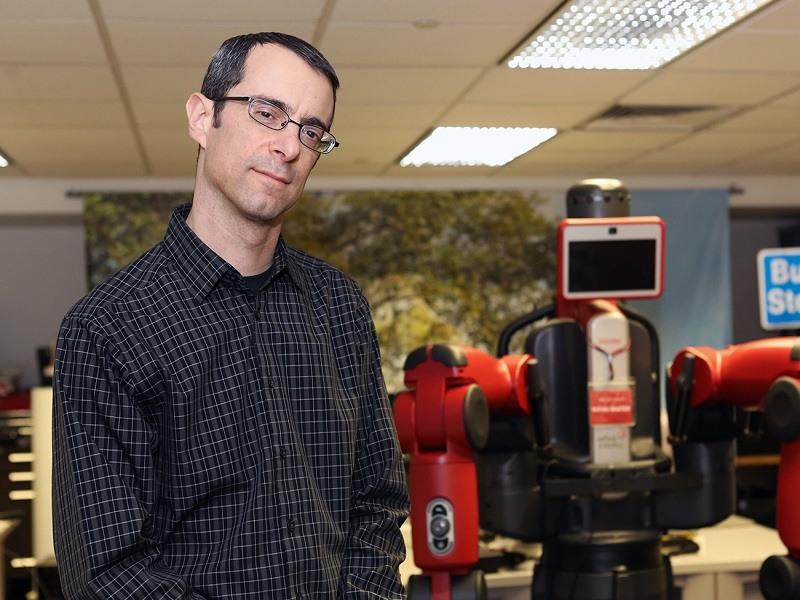 Aaron Steinfeld in a black shirt standing in front of robotic equipment.