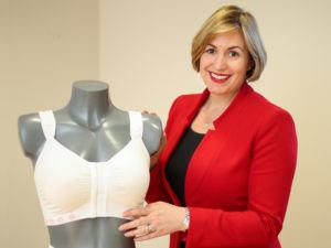 Ciara Donlon in red blazer standing next to one of her post-surgical bra products on a mannequin
