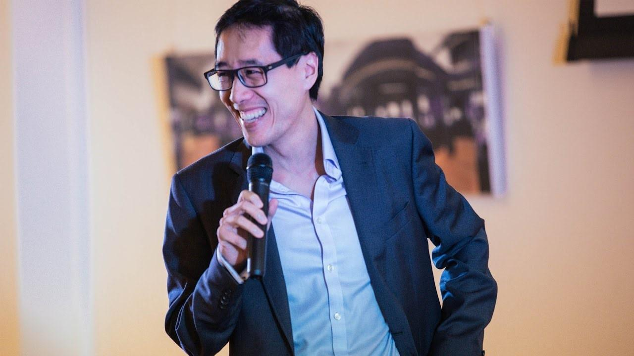 Huy Nguyen Trieu wearing a shirt and blazer speaks into a handheld microphone.