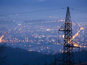 image of electricity pylons over a city at night time