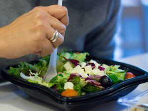 Salad in a black plastic container