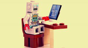 Toy robot working on a laptop as automation becomes more prevalent in the future of work