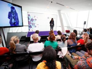 Researchfest finalist Bhagya Rekha Jonnala stands on a purple Inspirefest-branded stage presenting her research to a captive audience