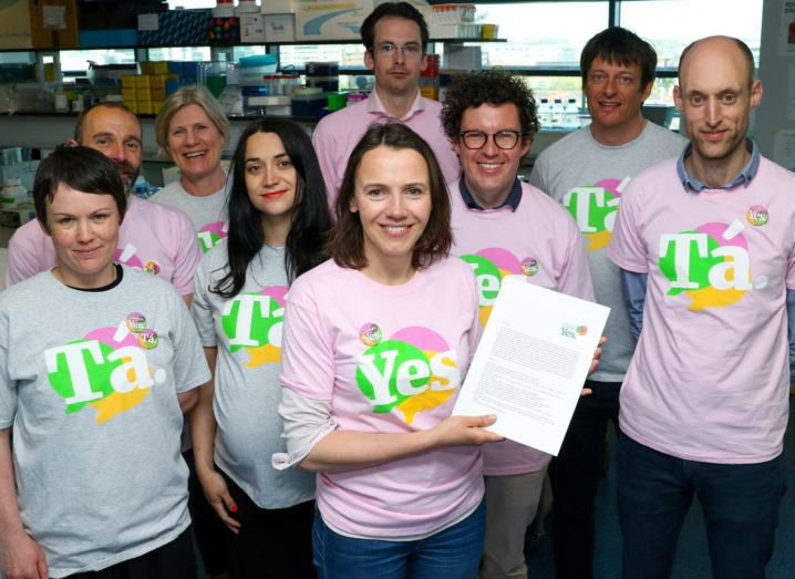 A group of men and women of varying ages wear grey and pink T-shirts saying 'Tá' and 'Yes'. The woman in front holds a printed letter in her hands.
